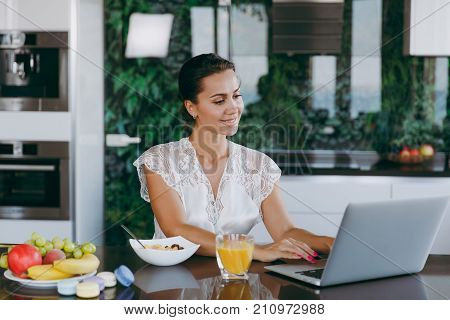 Portrait Of Beautiful Happy Woman Working With Laptop While Breakfast With Cereals And Milk. Eating