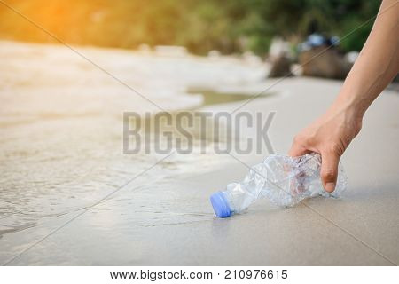 Hand woman picking up plastic bottle cleaning on the beach volunteer concept