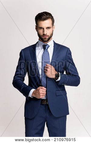 Hard to stand this handsome. Handsome young man adjusting his jacket and looking at camera while standing against white background.