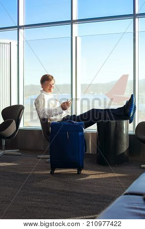 Caucasian man in early fifties side profile sitting legs up in airport terminal checking cellphone airplanes in background on tarmac