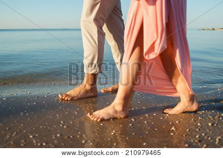 Legs on beach. Two lovers, man and woman barefoot near the water.