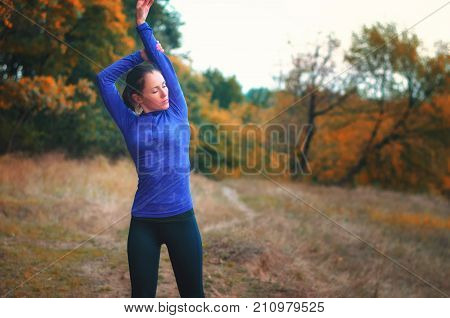 Caucasian Athletic Girl In Blue Shirt  Performs Warming-up Raised Her Hands Up  Before Jogging On Th