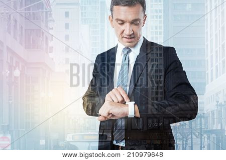 On schedule. Nice positive busy businessman looking at his watch and checking time while having a business meeting
