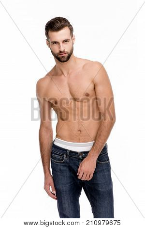 Shirtless and handsome. Handsome shirtless young man in jeans looking at camera while standing against white background.