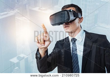 Sensory panel. Serious nice successful businessman wearing 3d glasses and pressing his finger to the sensory screen while being in a virtual reality