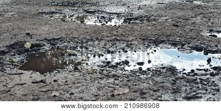 The panorama of pothole on the asphalt road. The end of bad road and happy ending