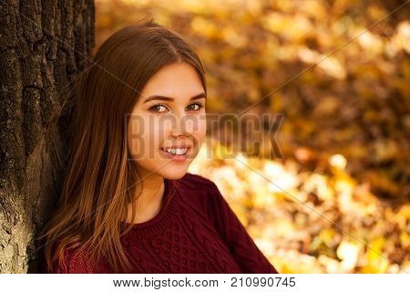Young beautiful brunette woman in autumn park