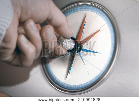 Hand turning an orientation knob on a compass to change course. Concept of career shift. Composite image between a hand photography and a 3D background.