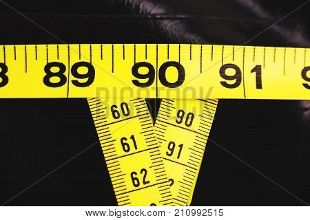 Three measuring tapes showing 90-60-90 as ideal parameters for women