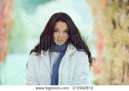 Autumn Beauty. Romantic woman in the Autumn Park Outdoors in Sunny Day. Portrait of happy lovely and beautiful mixed race Asian Caucasian young girl outdoor against blurred bokeh nature background. Model in white casual clothes looking at camera in sunny