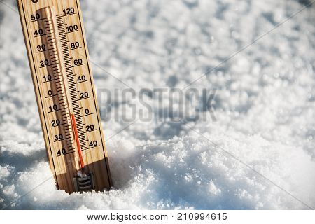 thermometer with a temperature above zero in the snow