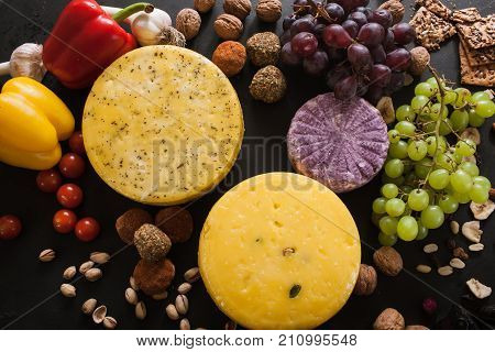 Food composition of dairy gourmet products, top view. Quality sorts of cheese with variety of appetizers and vegetables around
