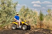 Caucasian man in sport protective goggles riding an ATV quad bike over rough terrain with meadows of dry autumn grass. Adventure activity concept. poster