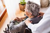 Health visitor and a senior woman during home visit. Unrecognizable nurse giving woman shoulder massage. poster