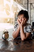 Asian women 40s white skin plump body in black and white shirt have a bored and unhappy gesture between waiting something in a coffee shop cafe with a clock vintage style poster