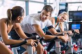Young people talking and smiling while working out on bike at gym. Friends in a conversation while cycling on stationary bike in fitness centre. Group of happy people working out at spinning class. poster