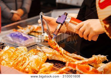 Hand Of Chef Using Burner Cooking And Burn King Crab Legs And Giant Prawns On Stove To Sale For Cust