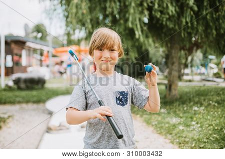 Young Little Boy Playing Mini Golf, Child Enjoying Summer Vacation