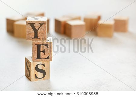 Three Wooden Cubes With Letters Aaa Means Ccc , On White Table, More In Background, Space For Text I