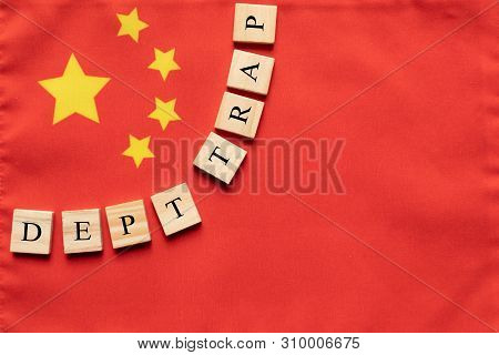 Concept Of Dept Trap In Wooden Block Letters On Chinese Flag.