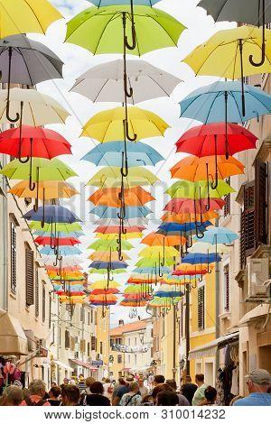 Novigrad, Istria, Croatia, Europe - September 3, 2017 - Tourists Walking Through An Alleyway With Co
