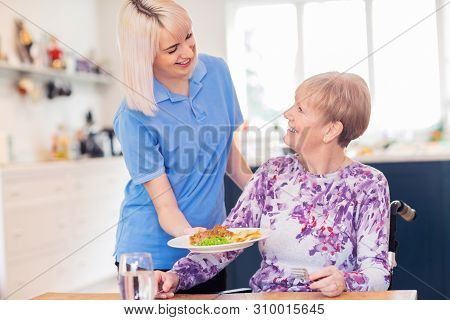 Female Care Assistant Serving Meal To Senior Woman Seated In Wheelchair At Table