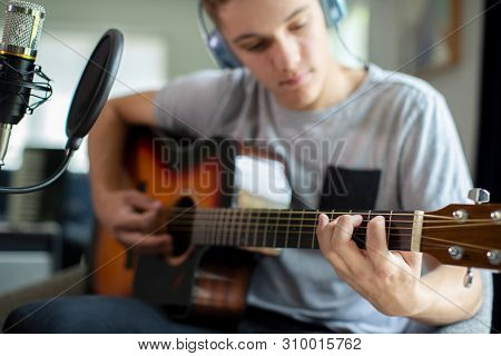 Teenage Boy Playing Guitar And Recording Music At Home