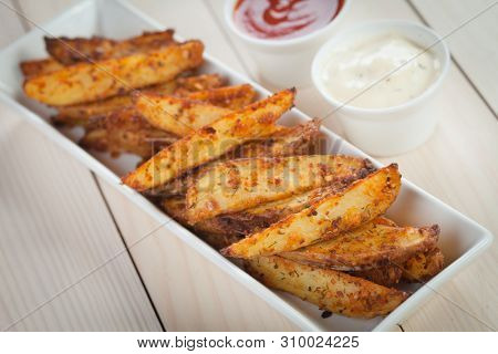Roasted spicy potato wedges served with ketchup and mayonnaise