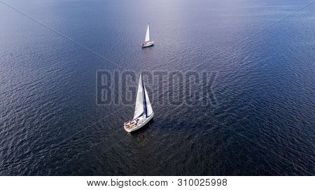 Aerial View From The Drone Of The Yachts With White Sails At Sea.