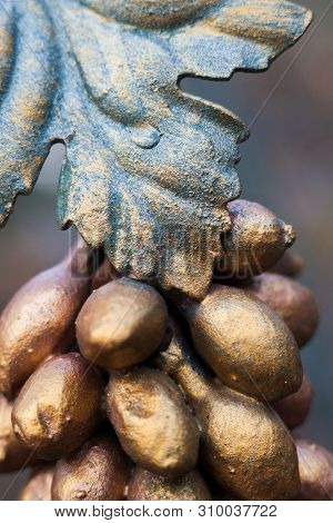 Metal Grapes Bunch And Leaf. Forged Ornament. Painted In Bronze Color. Close-up.