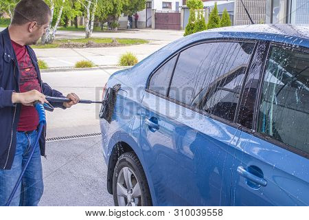 poster of Manual car wash with pressurized water in car wash outside.Using a brush to wash a car on a car washing facility on sunny summer day.Blue car manual wash of with pressurized water in car wash outside.