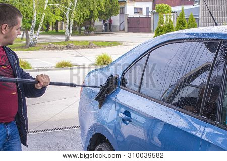 Using A Brush To Wash A Car On A Car Washing Facility On Sunny Summer Day.manual Car Wash With Press