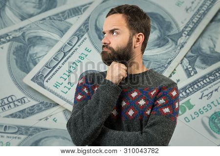 A Pensive Guy With A Beard Against A Background With Dollars Ponders What To Do Next. Thinking About