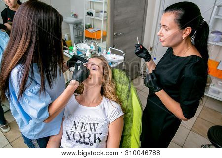 Beautician with assistant injects botulinum toxin injections in the womans forehead. Young woman on cosmetological procedures. Beauty and wellness. Horizontal photo. poster