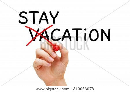 Hand Turning The Word Vacation Into Staycation. Concept About Spending A Holiday At Home Or Nearby R