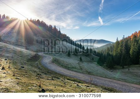 Dirt Road In Mountain At Sunrise. Wonderful Autumn Landscape With Fog In The Distant Valley. Hoarfro