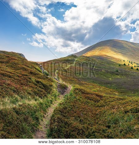 Trail Uphill Through The Mountain Ridge To The Top. Sunny August Weather With Clouds On The Blue Sky