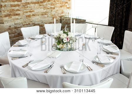 Wedding Table Setting Decorated With Fresh Flowers. White Plates, Silverware, White Tablecloth And W