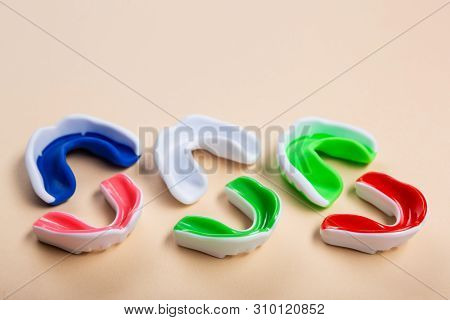 Mouth Guards For Boxing Or Karate Lie On A Beige Background, Three Large Mouth Guards And Three Smal