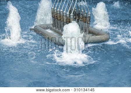 Closeup Of Fountain Nozzles With Water Sprays And Splashes. Aqua Geysers In Pool Of Waterworks