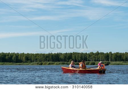 Family Rides A Wooden Boat On The Lake In Good Weather On Vacation, Active Holidays