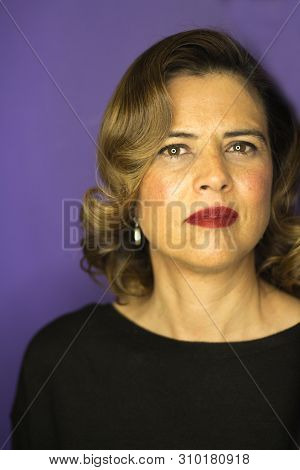 Middleaged Woman With Wavy Brown Hair. Serious Expression