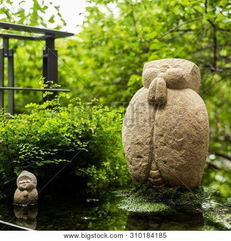 rough stone statue of Earth Store Bodhisattva(k?itigarbha bodhisattva) near a pond