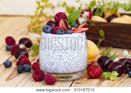 Chia Seed Pudding With Berries On Wooden Table. Rustic Stile Healthy Breakfast. Chia Seed With Milk,