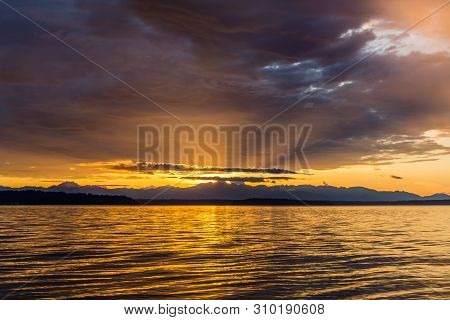 Dark clouds hang over the setting sun in the Pacific Northwest. poster
