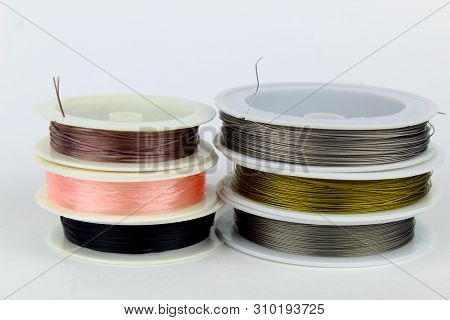 Colored Wire For Making Jewelry From Natural Stones And Natural Materials. Wire On White Plastic Coi