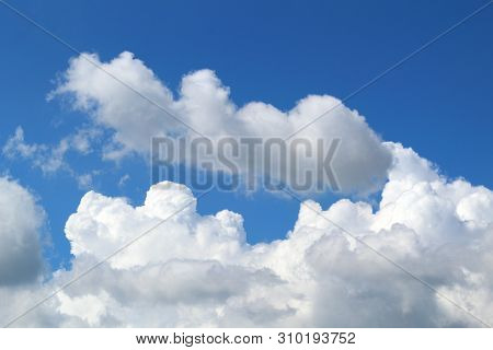 White Dense Cumulus Clouds On A Bright Sunny Day Against The Blue Sky.