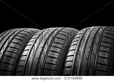 Studio Shot Of A Set Of Summer Car Tires Isolated On Black Background. Tire Stack Background. Car Ty