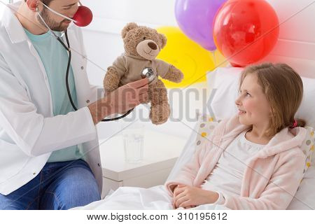 Young Volunteer Playing With A Sick Child