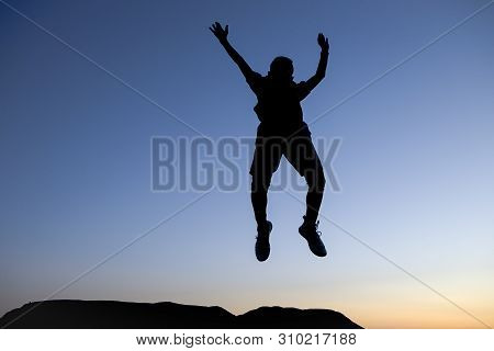 Silhouette Of Boy Leaping In The Air. A Boy In Silhouette Of Sunset Leaps In The Air In Excitement A